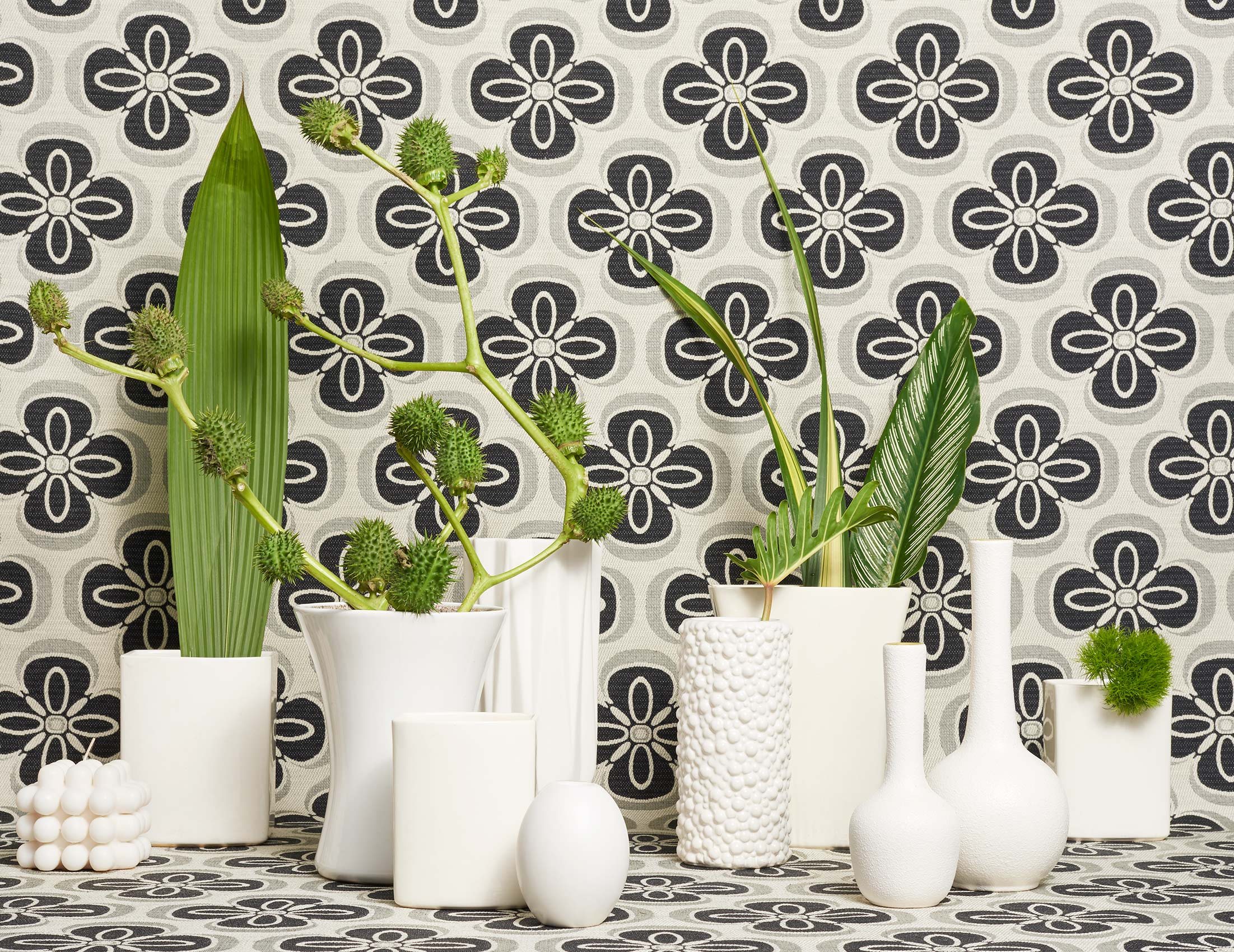 Various green leaves in different shaped white textured vases with black floral printed fabric background still life